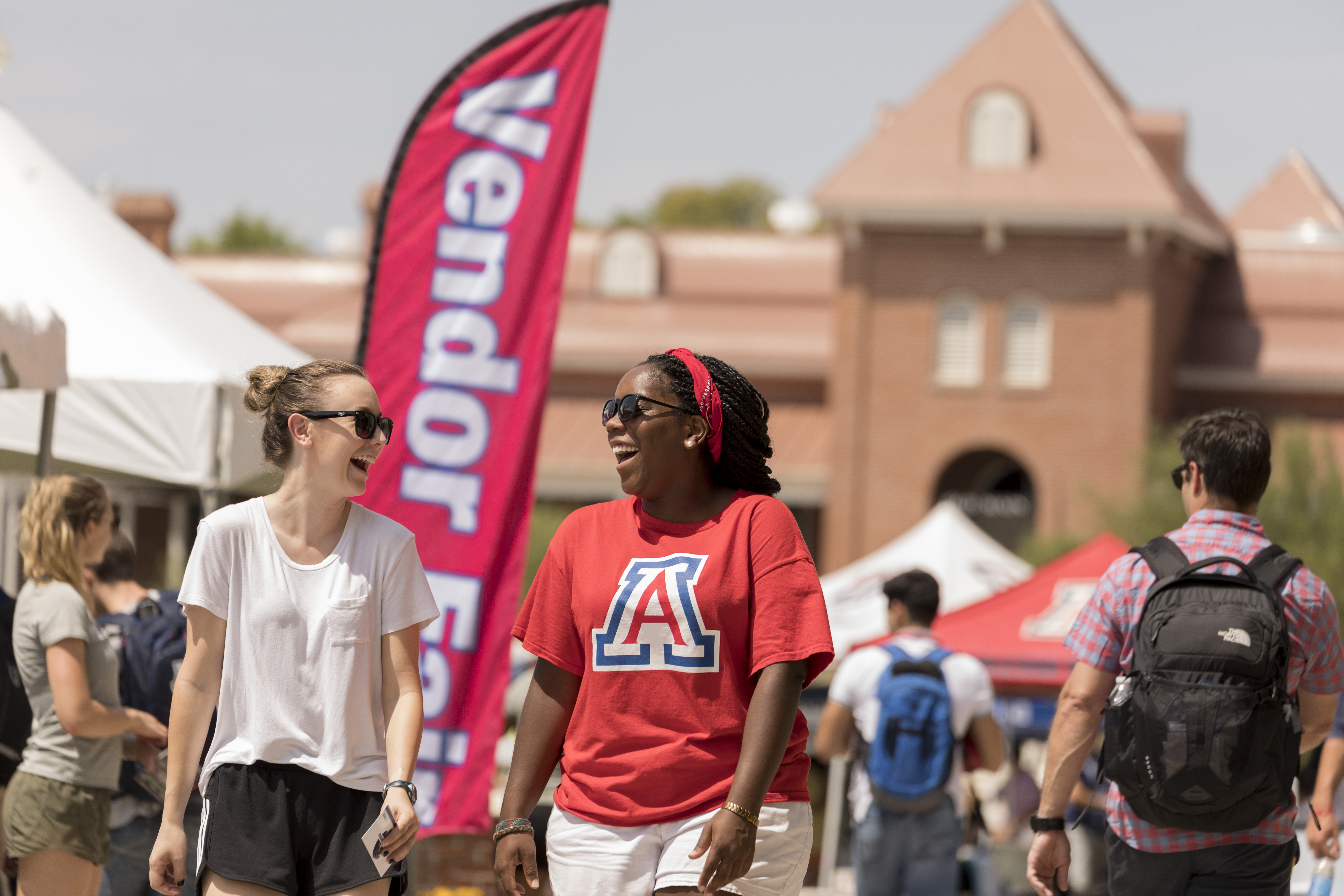 Two students walking at an event on the University of Arizona Mall